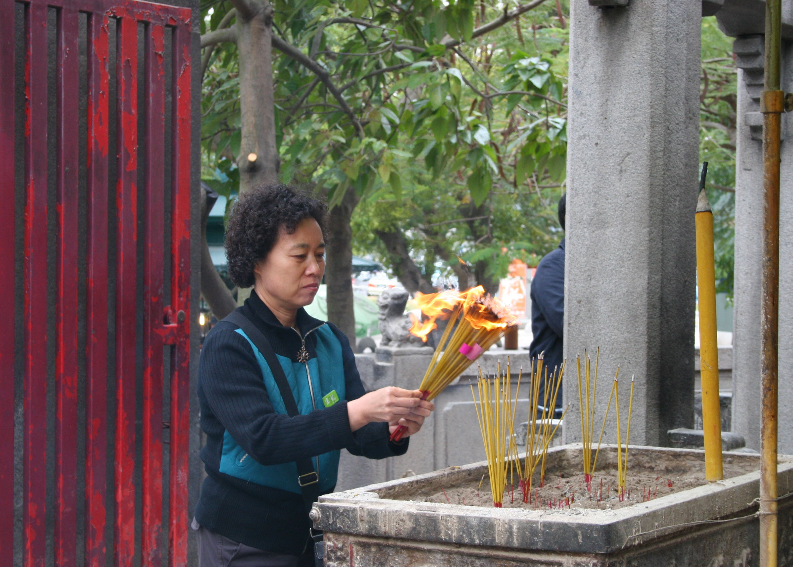 Woman lighting joss sticks at A-Ma Temple